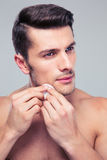 Man cleaning face skin with batting cotton pads. Over gray background stock photography