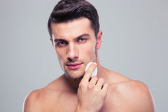 Man cleaning face skin with batting cotton pads. Over gray background Royalty Free Stock Images