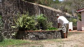 A man cleaning a fish pond in the tropics stock footage