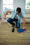 Man cleaning the floor with broom and dust picker. At home Stock Photography