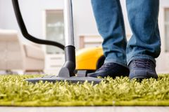 The man cleaning the floor carpet with a vacuum cleaner close up Royalty Free Stock Images