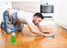 Man cleaning floor. Handsome young man wiping parquet floor. Husband housekeeping and cleaning concept. Home interior and kitchen in background royalty free stock photos