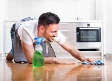 Man cleaning floor. Happy handsome man wiping parquet floor. Husband housekeeping and cleaning concept. Home interior and kitchen in background stock photos
