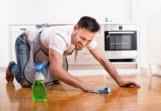 Man cleaning floor. Happy handsome man wiping parquet floor. Husband housekeeping and cleaning concept. Home interior and kitchen in background Royalty Free Stock Photography