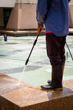 A man cleaning floor with high pressure water jet Stock Photo