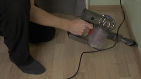 Man cleaning floor at home by wireless vacuum cleaner after repairing. Man take out dirt from floor at home room. High angle overhead shot stock video