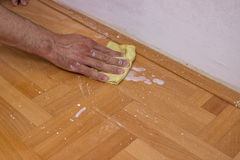 Man cleaning floor after painting wall. With roller Stock Photos