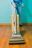 Man cleaning floor with vintage vacuum cleaner. Man cleaning wooden floor with vintage vacuum cleaner against turquoise wall Stock Images