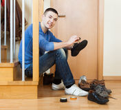Man  cleaning footwear. Smiling man sitting on stairs and cleaning footwear Stock Photo