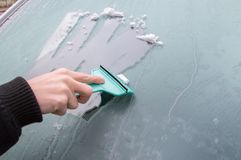 Man is cleaning frozen car window with ice scraper. Royalty Free Stock Image
