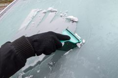 Man is cleaning frozen car window with ice scraper. Stock Photos
