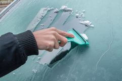 Man is cleaning frozen car window with ice scraper. Stock Photography