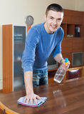 Man cleaning furniture with cleanser and rag at living room. Smiling man cleaning furniture with cleanser and rag at living room Stock Images