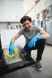 Man cleaning gas oven in kitchen. At home stock photos
