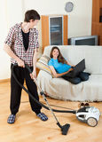 Man cleaning  while girl lying with notebook Royalty Free Stock Photography