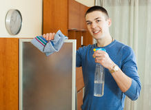 Man cleaning  glass with rag and cleanser at home Stock Photo