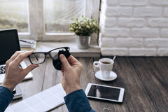 Man cleaning glasses. Man sitting at desk at home and cleaning his glasses with a cloth Stock Image