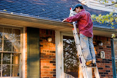 Man Cleaning Gutters stock image
