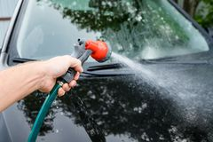 Man cleaning his car in self serve carwash, brush leaving shampoo strokes on front headlight.washing automobile at. Man cleaning his car in self serve carwash Royalty Free Stock Images