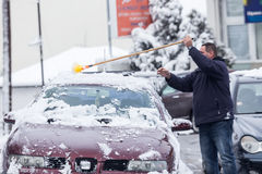 Man cleaning his car from the snow Stock Images
