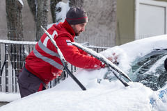Man cleaning his car from the snow Stock Image