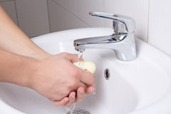 Man cleaning his hands in bathroom Stock Photography