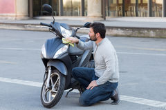 Man cleaning his scooter Royalty Free Stock Photo