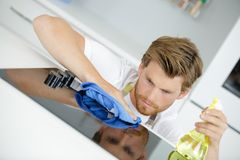 Man cleaning the hob. Hob stock images