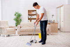The man cleaning home with broom. Man cleaning home with broom Stock Images
