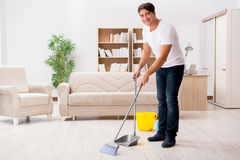 The man cleaning home with broom. Man cleaning home with broom Stock Image