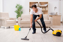 The man cleaning home with vacuum cleaner Stock Photos