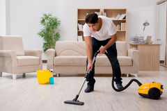 The man cleaning home with vacuum cleaner Royalty Free Stock Photos