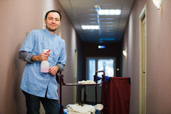 Man cleaning hotel hall wearing blue coat Royalty Free Stock Photography