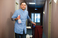 Man cleaning hotel hall wearing blue coat Royalty Free Stock Image