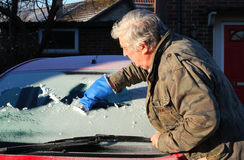 Man cleaning ice from his car window. Royalty Free Stock Photo