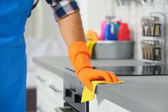 Man cleaning kitchen counter with rag. Closeup stock images