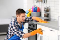 Man cleaning kitchen counter with rag. In house stock photo