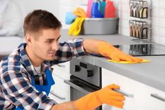 Man cleaning kitchen counter with rag. In house stock photography