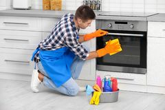 Man cleaning kitchen oven with rag. In house royalty free stock photos