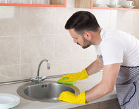 Man cleaning kitchen sink. Young handsome man with apron and protective gloves wiping sink in kitchen. Husband doing chores stock photo