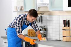 Man cleaning kitchen stove with sponge. In house royalty free stock photos