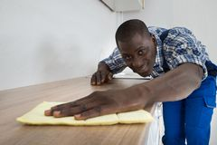 Man Cleaning Kitchen Worktop Stock Image