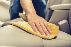A man cleaning leather car seat with microfiber cloth. Auto detailing and valeting concept Royalty Free Stock Photo