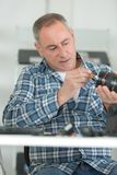 Man cleaning lens by brush. Lens stock photography