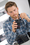 Man cleaning lens digital camera with special brush Royalty Free Stock Image
