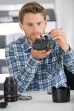 Man cleaning lens digital camera with special brush Royalty Free Stock Images