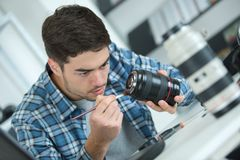 Man cleaning lens digital camera with special brush Stock Photos