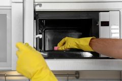 Man cleaning microwave oven in kitchen. Closeup royalty free stock photography