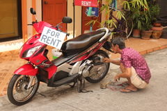Man Cleaning Motorcylce for Rent Stock Image