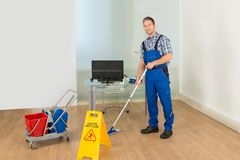 Man cleaning office floor Stock Images